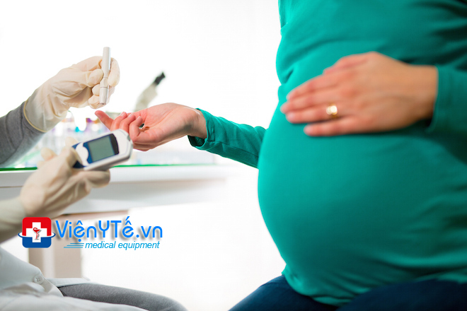 A close-up of a pregnant woman having her blood sugar/ G...L...U...C..O...S...E... checked.