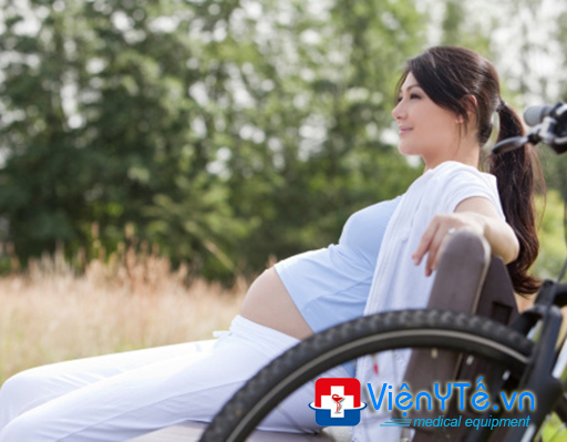 Pregnant woman sitting on bench with mountainbike next to her
